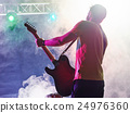 Rock band performs on stage. Guitarist. 24976360