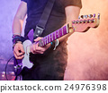 Rock band performs on stage. Guitarist. 24976398