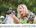 Beautiful blond woman with dog in green garden 24978196