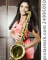 young pretty woman with saxophone playing on party 24995050