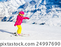 Little child skiing in the mountains 24997690
