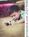 Asian boy taking photographs by camera.  25079086