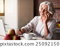 Old woman talking on the phone while taking notes 25092150