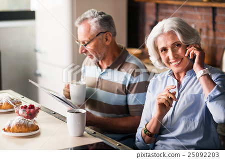 Smiley retired couple having morning coffee in the 25092203
