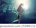 Retro microphone over the musician playing the guitar on band background with spot light, musical concept 25096132