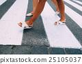 Female legs in white shoes going on zebra 25105037