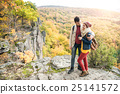 Young couple on a walk in sunny autumn forest 25141572