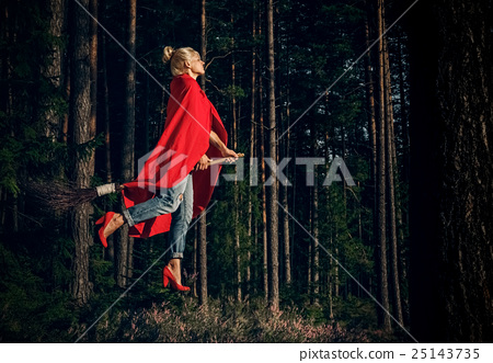 Modern witch blond in jeans and red cape flying on 25143735