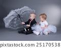 little boy and girl sitting under umbrella 25170538