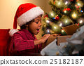 Joyful black boy opens present. 25182187