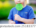 Child with allergic reaction eating big green lollipop 25183377