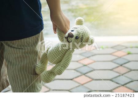 the kid hand holding a cute teddy bear 25187423