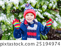 Happy kid boy having fun with snow in winter 25194974