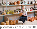 Portrait of glad woman pottery worker with ceramic crockery 25276101
