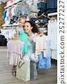Positive woman with small daughter holding clothes 25277227
