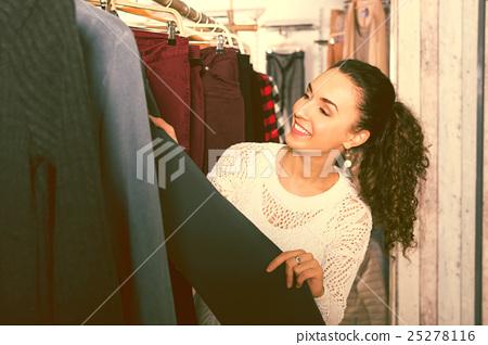 Happy female brunette choosing new trousers 25278116