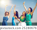 girls looking at the sea with hands up 25280676
