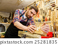 carpenter working with plane and wood at workshop 25281835