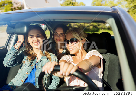 Stock Photo: happy teenage girls or young women driving in car