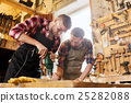 carpenters with drill drilling plank at workshop 25282088