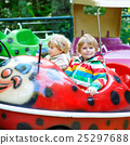 Two little kid boys on carousel in amusement park 25297688