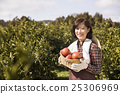 Middleaged Asian Female Farmer Holding a Basketful of Apples 25306969