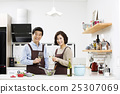 Middleaged Asian Couple Having White Wine in Kitchen 25307069