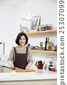 Middleaged Asian Woman Cutting Baguette in Kitchen 25307099