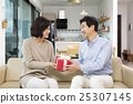 Middleaged Asian Man Giving a Red Gift Box to his Wife in the Living room 25307145