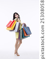 A young woman carrying a bunch of shopping bags 25308058