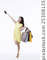 A young woman carrying a bunch of shopping bags 25308135