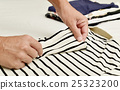 young man folding clothes 25323200