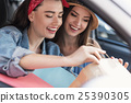 women sitting in a car with their purchases 25390305