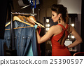 Seductive female model choosing clothes backstage 25390597