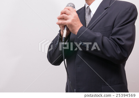 A man with a suit to talk in front of the microphone 25394569