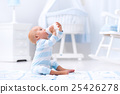 Baby boy drinking milk in sunny nursery 25426278