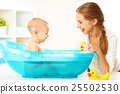 Happy family mother bathes the baby in  bath 25502530