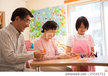 요양 시설의 리쿠에 인증 룸에서 종이 접기를 즐길 노인과 젊은 개호 직원 25541711