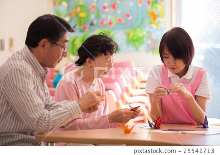 요양 시설의 리쿠에 인증 룸에서 종이 접기를 즐길 노인 두 명과 젊은 개호 직원 25541713