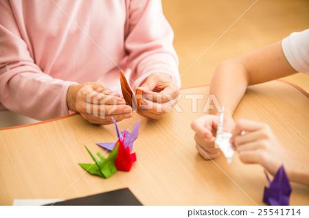 요양 시설의 리쿠에 인증 룸에서 종이 접기를 즐길 노인과 젊은 개호 직원 25541714