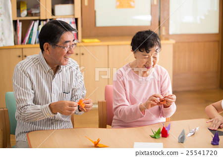 요양 시설의 리쿠에 인증 룸에서 종이 접기를 즐길 두 노인 25541720