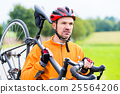 Cyclist carrying his bike over shoulder 25564206