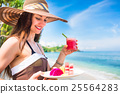 woman at tropical beach eating fruit for breakfast 25564283