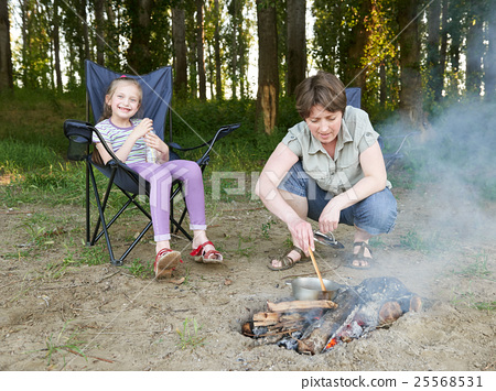 woman cooking food, people camping in forest 25568531