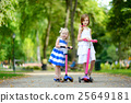 Two adorable little sisters wearing beautiful dresses riding their scooters 25649181