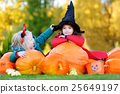 Little girls wearing halloween costume on a pumpkin patch 25649197