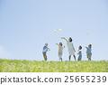 นักเรียนระดับประถมศึกษาและครูที่บินเครื่องบินกระดาษในทุ่งหญ้า 25655239