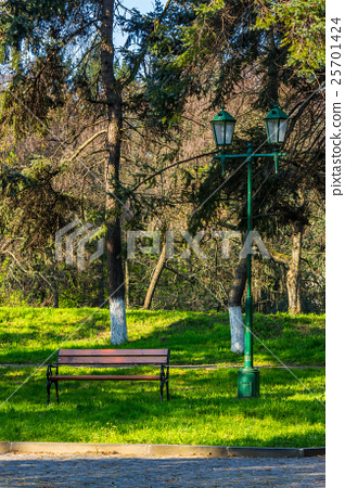 old city park with bench and lantern 25701424