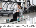 Concentrated woman stretching after a workout 25745492