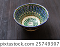 traditional central asian bowl on dark brown board 25749307